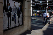 Men in shirtsleeves walk past a stylish clothing shop for businessmen on a poster in the City of London.
