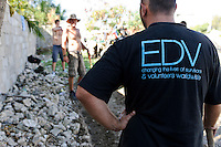 Andy Chaggar and volunteers working on a construction project at an orphanage supported by EDV, Port-au-Prince, Haiti. EDV is committed to affecting permanent change in disaster-affected communities worldwide. Their role is to facilitate personal connections between volunteers and the survivors of disasters.  The charity is based on a proven model developed by several landmark organisations that have paved the way for citizens to become disaster volunteers. These landmark organisations have shown that supposedly ordinary people working together with the guidance of knowledgeable leaders can make an extraordinary difference in the lives of those affected by disaster..EDV believe that to provide meaningful relief and reconstruction assistance to disaster affected communities they have to do more than reconstruct buildings. They need to understand and address the factors that made a community vulnerable to the disaster in the first place. The charity's work is organised with these factors in mind so that they can affect change that far outlives their presence..EDV believes that survivor motivation is essential to the recovery of any disaster-affected community. Their operations will always be predicated on the idea that survivors may be traumatised, but they are not helpless. With this in mind, EDV encourages host communities to direct their own recovery. EDV believe that this empowerment is essential in helping survivors feel a renewed sense of control over their lives which will, in turn, help overcome the feelings of hopelessness that can follow a disaster and inhibit long term recovery. EDV also believe that social cohesion is of primary importance in any disaster-affected area. No amount of bricks or mortar will bring about sustainable improvement if communities fail to come together or are disrupted by relief efforts. Therefore, their operations will always aim to foster communication and cooperation within and between the communities they serve.