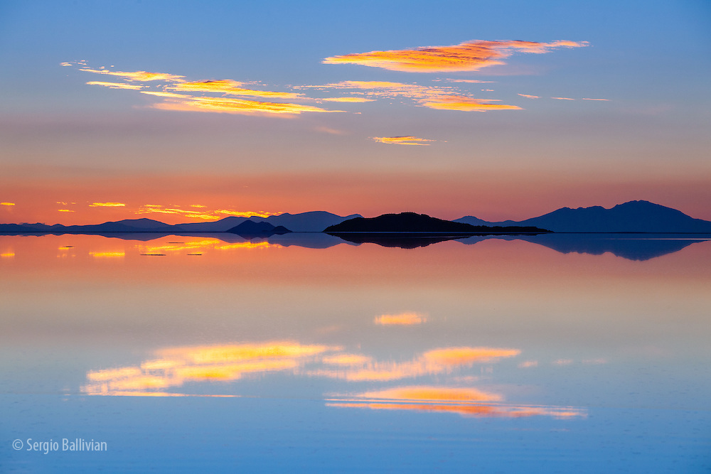 The Salar de Uyuni in flood creates the perfect conditions for mirror-reflections at sunset during the wet season in Bolivia's high-altitude Altiplano.