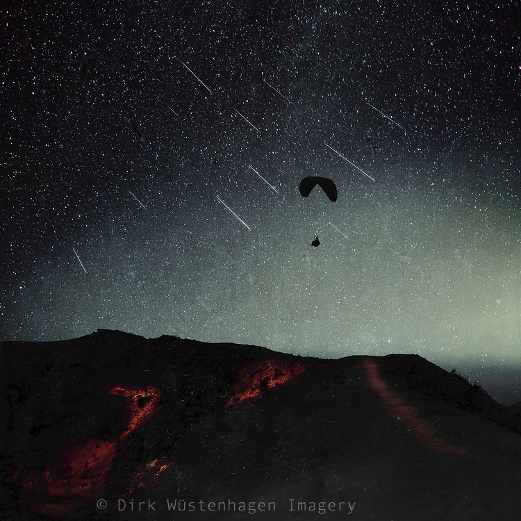 Surreal nightscape with paraglider and falling stars<br />