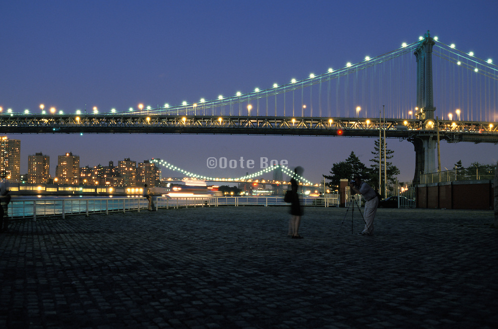 Lights on the Manhattan bridge at night with the Williamsburg Bridge in the background