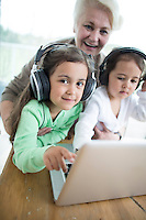 Portrait of happy senior woman with granddaughters listening to music while using laptop