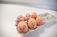 Six-pack eggs with faces painted in a egg carton