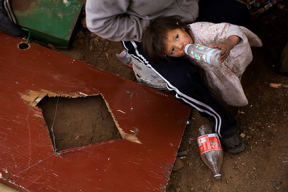A young girl drinks water  on her mother's lap. She and her family have been sleeping outside since their tin and cardboard shack burned to the ground two weeks before. Even before the accident the family had no water or electricity and their only source of income was selling scavenged trash.