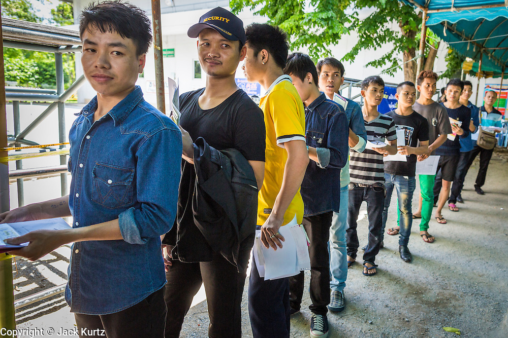 """17 JULY 2014 - BANGKOK, THAILAND: Undocumented Cambodian workers line up for their ID cards at the temporary """"one stop service center"""" in the Bangkok Youth Center in central Bangkok. Thai immigration officials have opened several temporary """"one stop service centers"""" in Bangkok to register undocumented immigrants and issue them temporary ID cards and work permits. The temporary centers will be open until August 14.    PHOTO BY JACK KURTZ"""