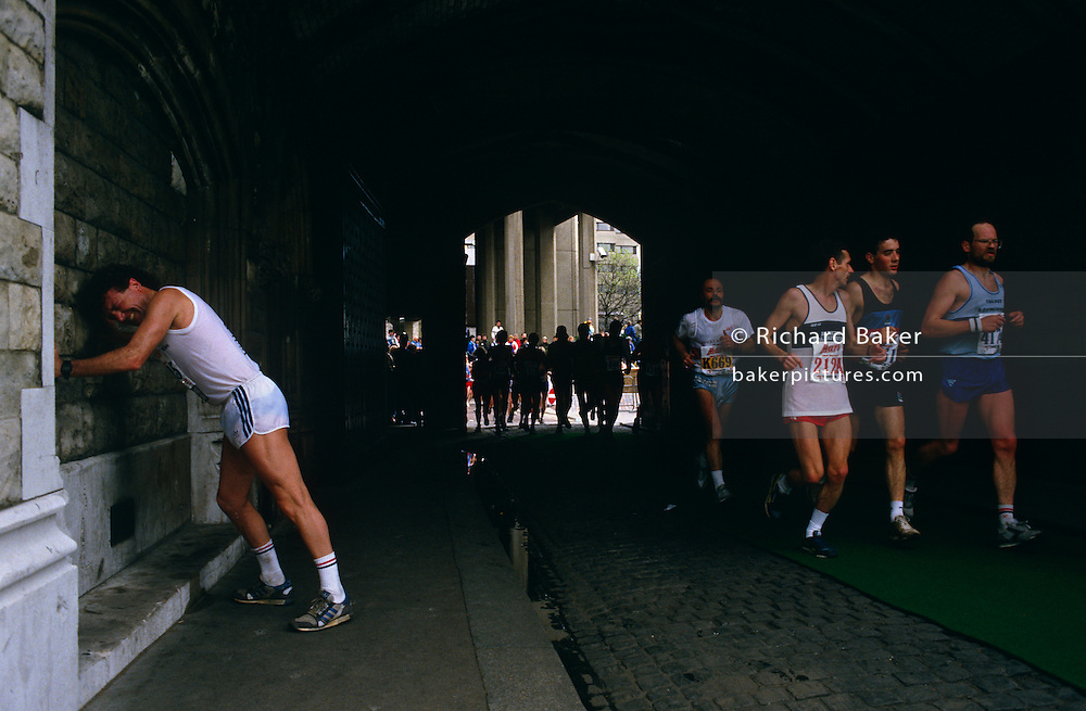 "A few miles from the finish line, this long-distance runner has stopped in agony to lean against the walls beneath Tower Bridge during th London Marathon, England. Pushing against the solid wall and stretching his cramped leg muscles, he grimaces in pain as other runners speed past on their way completing their personal race. Pushed to his limits, this man needs to continue a few more Kilometres to claim his medal and to claim victory. But he still has to overcome the pain of an overworked body. When glycogen runs low, the body must then burn stored fat for energy, which does not burn as readily. When this happens, the runner will experience dramatic fatigue. This is called ""hitting the wall""."