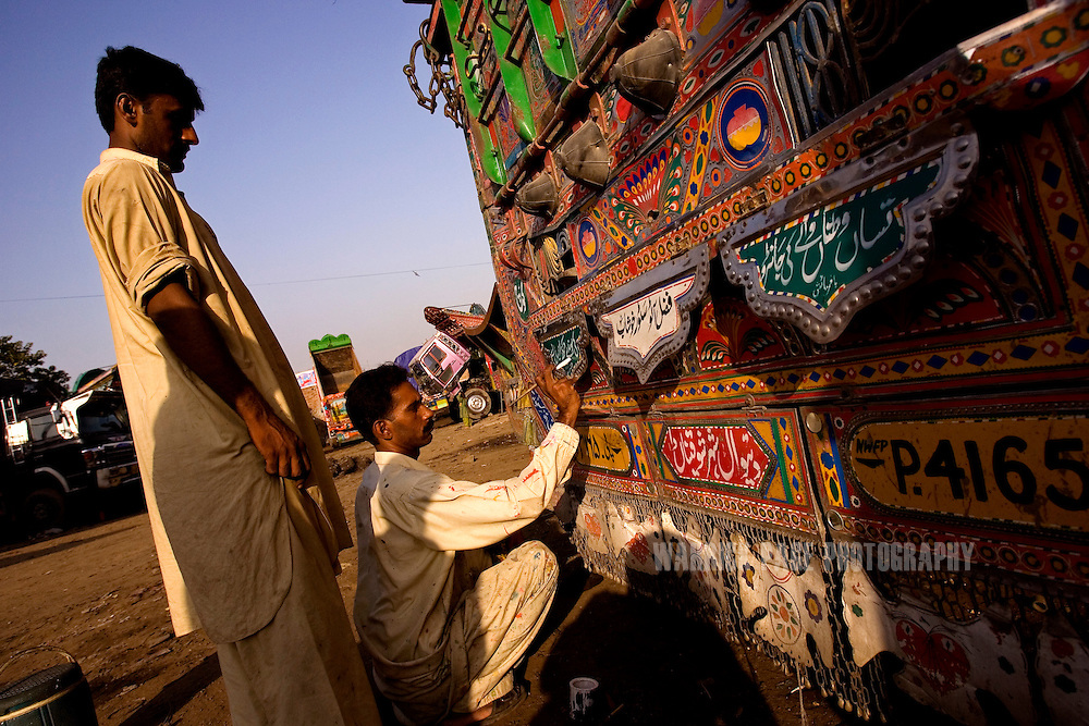RAWALPINDI, PAKISTAN - OCTOBER 9: A Pakistani truck-artist paints Urdu poetry on the bumper of a truck at a painting and repair yard, October 9, 2008, in Rawalpindi, Pakistan. The heavily adorned Bedford trucks have become a national icon and cost upwards of one million rupees (USD$12,500) for a full makeover. Much of the artwork consists of a cultural mix of religious and secular, Pakistani film and music stars, cricket legends, romanticized military imagery of F-16 fighter jets and Ghauri missiles, the Prophet's winged horse, Buraq, and dreamlike scenes of wooded lakes and snow-capped mountains and exotic animals. (Photo by Warrick Page)