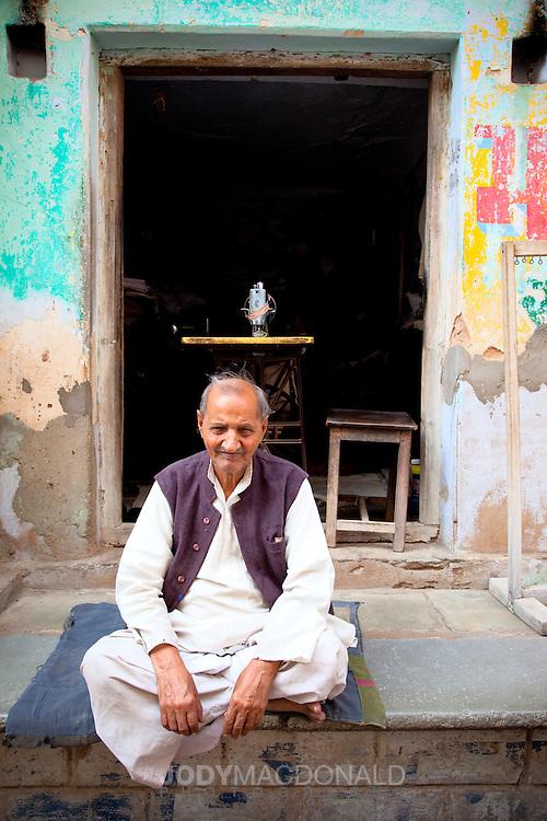 Man outside of textile shop in pushkar, India