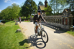 © London News Pictures. 15/05/2016. Windsor, UK. A competition rider, cycles between the stables and arena, through the grounds of Windsor Castle on the final day of the 2016 Royal Windsor Horse Show, held in the grounds of Windsor Castle in Berkshire, England. This years event is part of HRH Queen Elizabeth II's 90th birthday celebrations.  Photo credit: Ben Cawthra/LNP