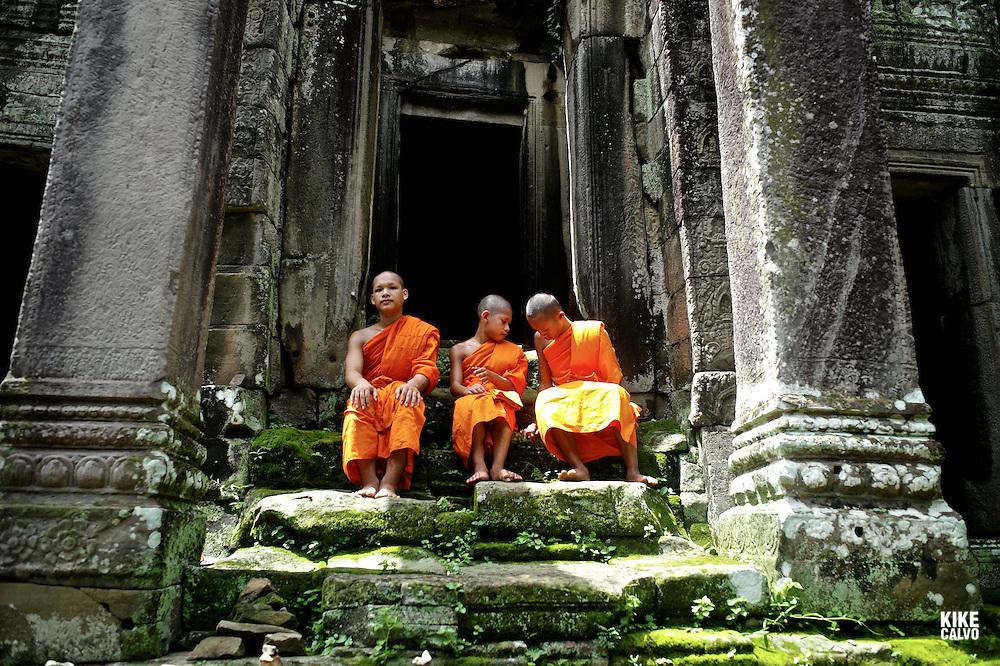 Theraveda Buddhist monks at the ancient ruins of Bayon Temple, Angkor, Cambodia.