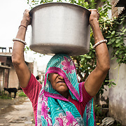 CAPTION: The water from community storage tanks is used for low-end uses such as washing. LOCATION: Devshree Nagar, Indore, Madhya Pradesh, India. INDIVIDUAL(S) PHOTOGRAPHED: Unknown (face covered, consent not required).