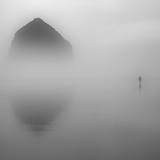 Etheral fog enshrouds Haystack Rock and a lone beachcomber.  Cannon Beach, Oregon.