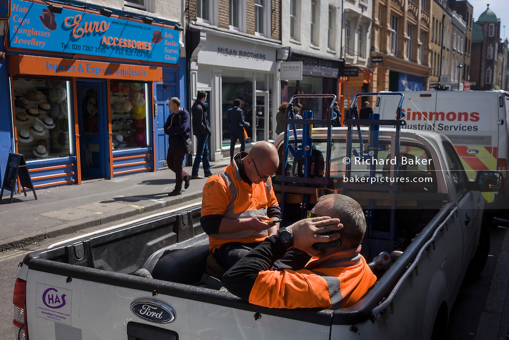 Two workmen sit in the back of their truck during a break of their shift in Soho, central London.