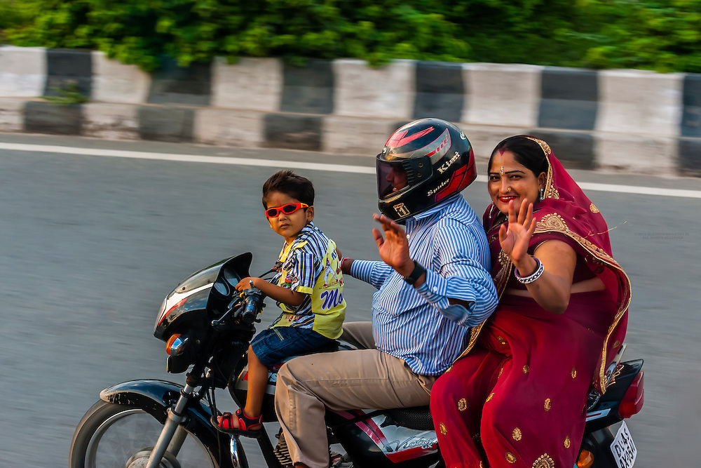 A family of three ride on a motorcycle on the Ring Road in Delhi, India.