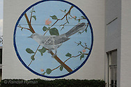 Outdoor mural depicts mockingbird on branch in hometown of Harper Lee, author of To Kill a Mockingbird; Monroeville, Alabama.