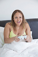 Young pregnant playing video game with remote control in bed