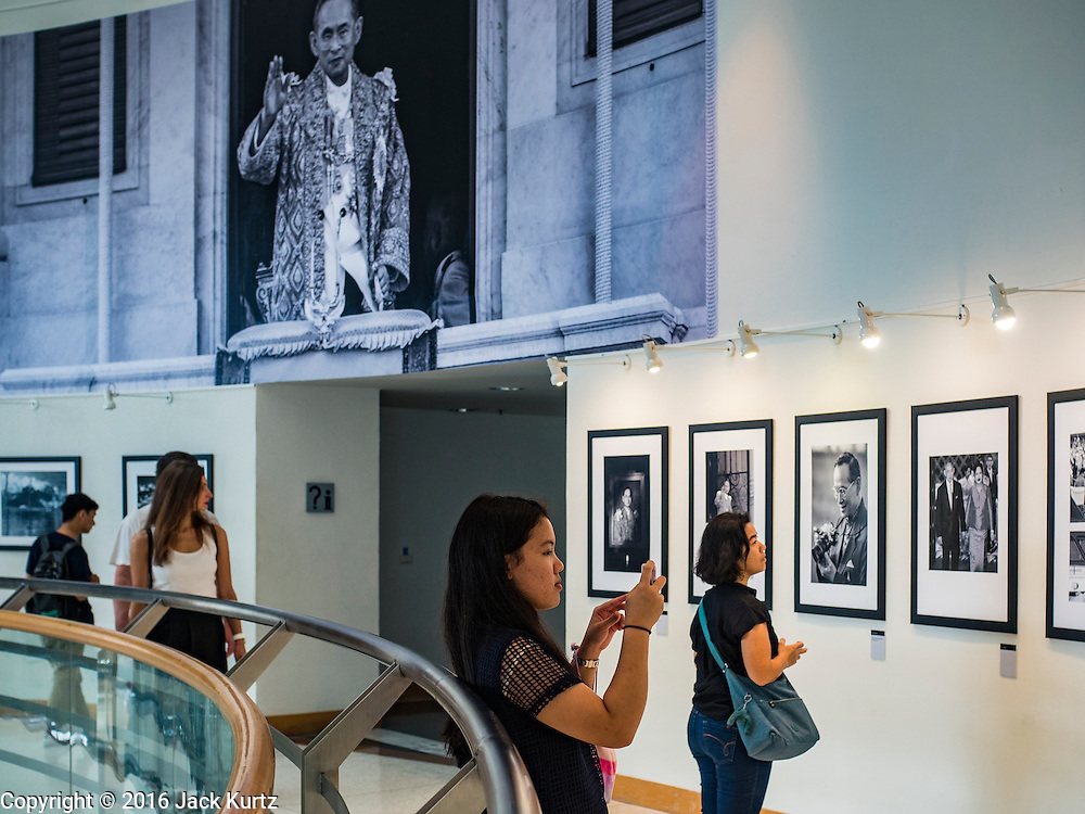 """06 NOVEMBER 2016 - BANGKOK, THAILAND: A Thai uses a smart phone to make a picture of one of the pictures in the photo exhibit honoring Bhumibol Adulyadej, the late King of Thailand. The Royal Photographic Society of Thailand with the Bangkok Art and Culture Centre and Thai Beverage Public Company Limited are hosting a photography exhibition to commemorate the late Thai King Bhumibol Adulyadej. The """"In Remembrance of His Majesty King Bhumibol Adulyadej"""" Photography Exhibition is dsiplaying 89 photographs by 89 photographers honoring King Bhumibol Adulyadej's legacy. The King was an avid photographer was usually seen with a camera in his hands. The exhibition will be on display until 27 November 2016 on the Curved Walls on the 3rd - 5th floor, Bangkok Art and Culture Centre.     PHOTO BY JACK KURTZ"""
