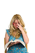 Young blond woman with red reading glasses reads a textbook