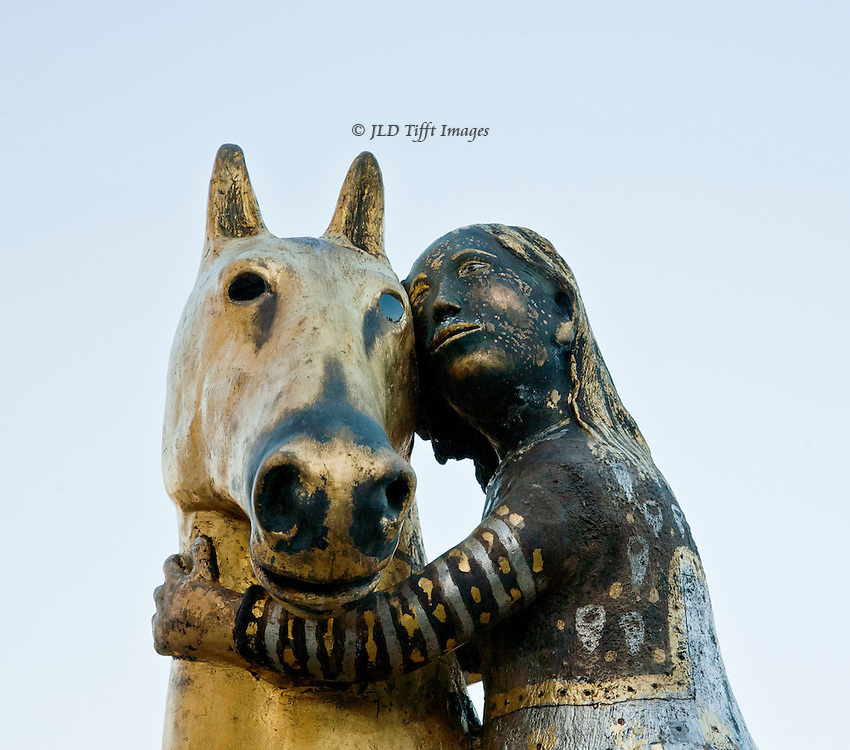Detail of a girl hugging her horse, showing both heads and her arm.  Bronze by Giuseppe Gavazzi in the Boboli Gardens, Florence, Italy.