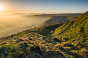 Curved ditch and ramparts around the summit of Mam Tor, the site of an Iron Age Hillfort. Looking over a misty Hope Valley. Winnats Pass and the Hope Valley Cement Works can be seen in the distance. Peak District landscape photography, Derbyshire, England, UK. March, 2014.