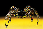 "As Mark Tilden's Spyder 1.0 approaches like a tiny but menacing arachnid, its circuits try to optimize actions, walking in this case, with minimal energy. Perturbed by the environment, its patented ""nervous net"" seeks the minimum state, its legs moving almost randomly until it succeeds. In 1990, Spyder 1.0 was the first walking robot to use Tilden's nervous net control system. When Tilden first achieved such complex behavior from such minimal components, the results astonished some roboticists. Los Alamos, NM. From the book Robo sapiens: Evolution of a New Species, page 118-119."