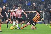 Hull City player Tommy Elphick (35) does sliding tackkle on Brentford forward Neal Maupay (9)  during the EFL Sky Bet Championship match between Hull City and Brentford at the KCOM Stadium, Kingston upon Hull, England on 15 December 2018.