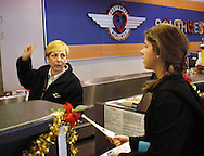 Southwest Airlines employee Deborah Stanchak (L) directs passenger Katie Reinprecht, 16, of North Wales, Pa, to her flight after handing giving her a boarding pass at Philadelphia International Airport December 29, 2005 in Philadelphia, Pennsylvania. (Photo by William Thomas Cain)