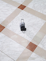 Suitcase and handbag on tiled floor elevated view