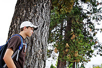 Bryce Volking, 15, waits for his dad at the end of a row of pine trees Tuesday after getting out of class at Coeur d'Alene High School.