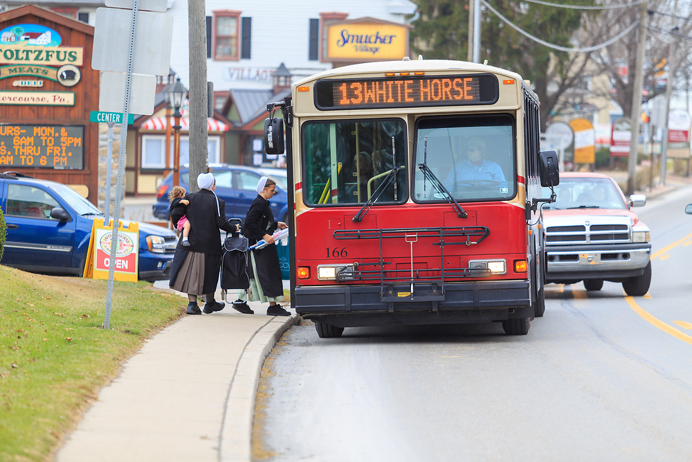 Intercourse, PA - December 1, 2014: Amish women and children board a bus on the Old Philadelphia Pike, the main street of the Lancaster County village.