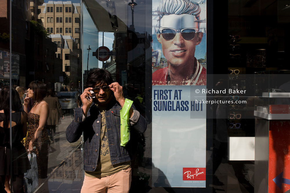 A man puts his sunglasses back on after cleaning with a poster of a model showing stylish shades outside a sunglasses shop window selling Ray Bans on Long Acre in London's Covent Garden.