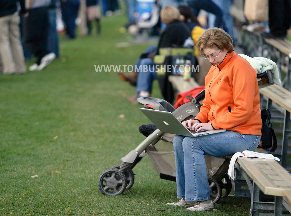 West Point, NY - A woman sitting by a stroller works on her laptop during a rugby match at the Anderson Rugby Center at the United State Military Academy on Nov. 21, 2009.