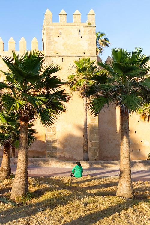 RABAT, MOROCCO - 27th May 2014 - Person wearing traditional Moroccan clothing sitting outside the Kasbah of the Udayas, Rabat Medina, Morocco.