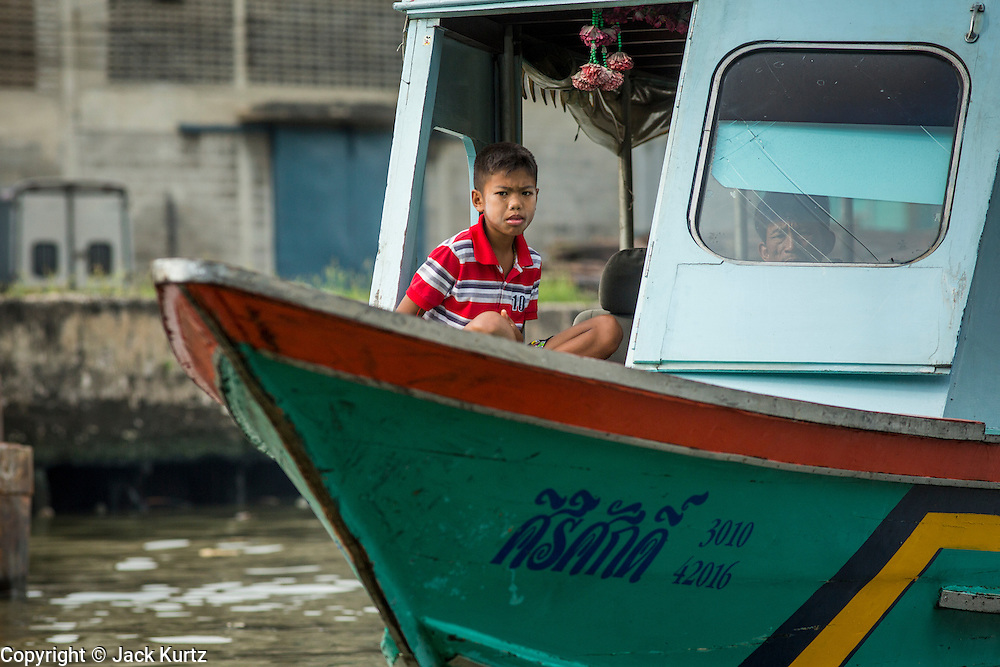 "17 NOVEMBER 2012 - BANGKOK, THAILAND:  A boy sits in the wheelhouse of his family boat on a canal in the Thonburi section of Bangkok. Bangkok used to be known as the ""Venice of the East"" because of the number of waterways the criss crossed the city. Now most of the waterways have been filled in but boats and ships still play an important role in daily life in Bangkok. Thousands of people commute to work daily on the Chao Phraya Express Boats and fast boats that ply Khlong Saen Saeb or use boats to get around on the canals on the Thonburi side of the river. Boats are used to haul commodities through the city to deep water ports for export.    PHOTO BY JACK KURTZ"