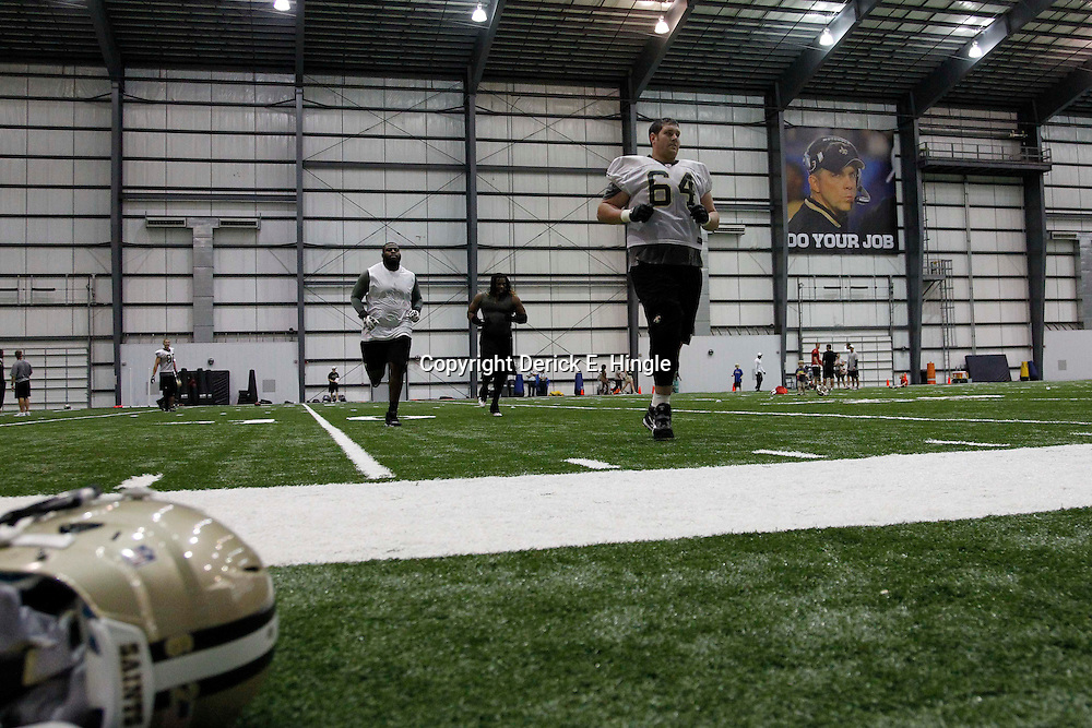 July 27, 2012; Metairie, LA, USA; A sign of New Orleans Saints head coach Sean Payton who was suspended by NFL commissioner Roger Goodell is seen over offensive tackle Zach Strief (64) as he runs sprints following a training camp practice at the team's indoor practice facility. Mandatory Credit: Derick E. Hingle-US PRESSWIRE