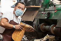 Portrait of a skilled cobbler with polishing machinery in workshop