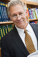 portrait of senior man wearing suit in library
