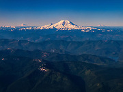 Three prominent Washington state volcanoes are visible over the Cascade foothills in this aerial view taken from over North Bend, Washington. In the center, Mount Rainier, with an elevation of 14,411 feet (4,392 meters), is the tallest mountain in Washington and the highest volcano in the Cascade Range. At left, Mount Adams, at 12276 ft. (3742 m), is the second-tallest mountain in the state. At right is Mount St. Helens, a 8,365 feet (2,550 m) volcano that lost nearly 15 percent of its height in a 1980 eruption. The body of water in the lower-right is the Howard A. Hanson reservoir, used for flood control and to provide drinking water to Tacoma.