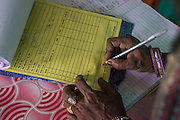 A producer group farmer signs a receipt after selling vegetables to the collection centre in Machahi village, Muzaffarpur, Bihar, India on October 27th, 2016. Non-profit organisation Technoserve works with women vegetable farmers in Muzaffarpur, providing technical support in forward linkage, streamlining their business models and linking them directly to an international market through Electronic Trading Platforms. Photograph by Suzanne Lee for Technoserve