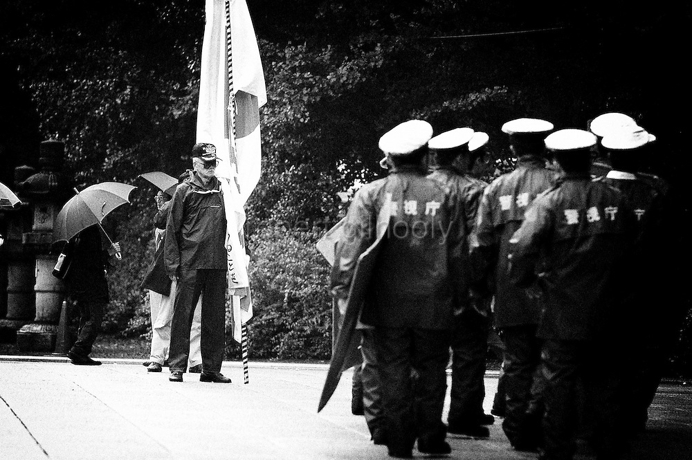 A Japanese nationalist holds Japan's national flag as metro police arrive in anticipation of a visit from Japan's prime minister to controversial Yasukuni Shrine in Tokyo, Japan. very year on August 15, the day Japan officially surrendered in WWII, tens of thousands of Japanese visit the controversial shrine to pay their respects to the 2.46 million war dead enshrined there, the majority of which are soldiers and others killed in WWII and including 14 Class A convicted war criminals, such as Japan's war-time prime minister Hideki Tojo. Each year speculation escalates as to whether the country's political leaders will visit the shrine, the last to do so being Junichiro Koizumi in 2005. Nationalism in Japan is reportedly on the rise, while sentiment against the nation by countries that suffered from Japan's wartime brutality, such as China, has been further aggravated by Japan's insistence on glossing over its wartime atrocities in school text books...Photographer:Robert Gilhooly..