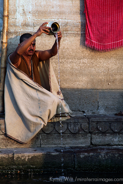 Asia, India, Varanasi. A man performs ritual prayer offering to the Ganges River, on the ghats at Varanasi.