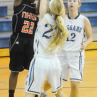 New Hanover's Ayonna Cotten passes around Hoggard's Rebekah Fry and Julia Buehler(background) Friday December 12, 2014 at Hoggard High School in Wilmington, N.C. (Jason A. Frizzelle)