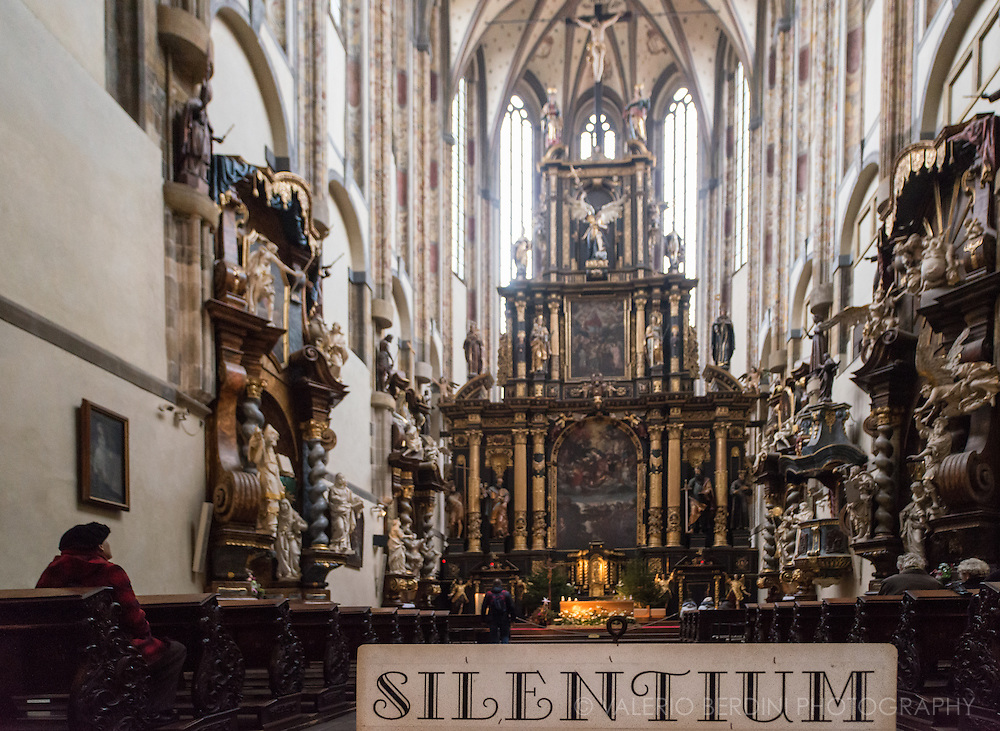 People praying in an old church in central Prague. A sign asks visitors for silence
