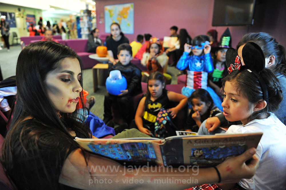 """Alisal High School senior Lesly Lopez reads """"A Gift for Abuelita"""" to kids in Halloween costumes at the César Chávez Library in Salinas. Lopez is the vice-president of the Book Club at Alisal."""