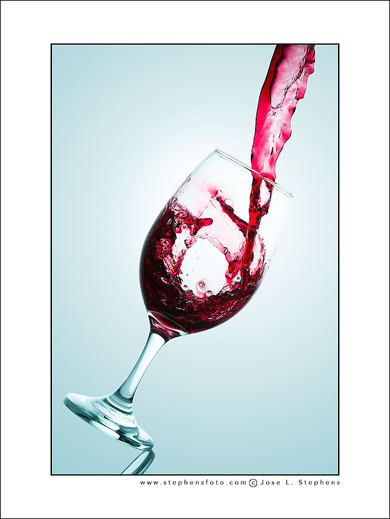 Wave formed on the pouring of red wine on a tasting glass against a blue background