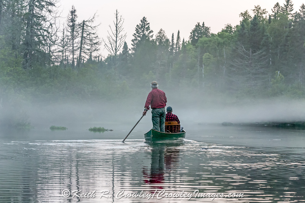 Brule River fishing guide Damian Wilmot poles upstream through the evening mist on the Brule near Lake Nebagamon, Wisconsin with angler Matson Holbrook in a 1895 Joe Lucius guide canoe Wilmot meticulously restored over the course of two years.