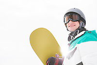 Smiling young man holding snowboard against clear sky