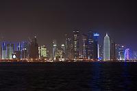 """08 APR 2013, DOHA/QATAR<br /> Downtown Doha mit den Hochhaeusern (auf der rechten Seite) Palm Towers, Tornado Tower, Al Bidda Tower, Qatar World Trade Center, und Doha Tower, auch """"Condom Tower"""" (rechts), gesehen von der Al Corniche Street<br /> IMAGE: 20130408-01-051<br /> KEYWORDS: Katar, Hochaus, Wolkenkratzer, Tower, Skyscraper, Nacht, Nachtaufnahme, night,"""