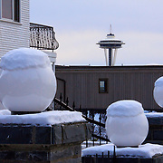 Snow covers white glass globe lights on top of stone fence columns with the Space Needle in background, Queen Anne hill, Seattle, Washington