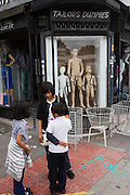 Three children echo the three sizes of a tailors mannequin shop in Whitechapel, East London.